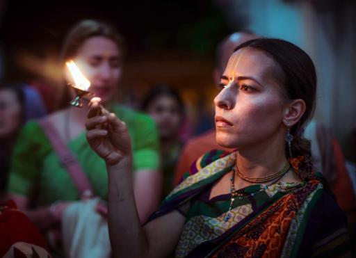 A devotee offering a candle as an offering to the Deities
