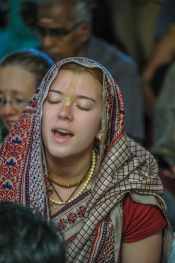 A devotee chanting in a kirtan